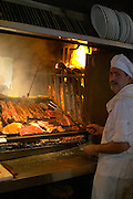 The gigantic huge charcoal grill with pieces of meat being cooked, the chef in white with a grilling fork, in the restaurant El Palenque, the sword fish swordfish, in the Mercado del Puerto, the market in the port harbour harbor where many people go and eat and shop on weekends Montevideo, Uruguay, South America