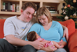 Young couple sitting together on sofa in living room holding baby,