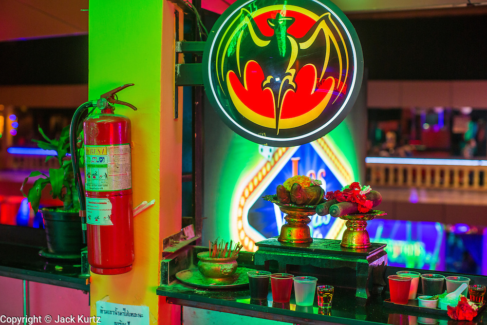 """12 JANUARY 2013 - BANGKOK, THAILAND:  A shrine in front of a go-go bar in the Nana Entertainment Plaza in Bangkok. Prostitution in Thailand is illegal, although in practice it is tolerated and partly regulated. Prostitution is practiced openly throughout the country. The number of prostitutes is difficult to determine, estimates vary widely. Since the Vietnam War, Thailand has gained international notoriety among travelers from many countries as a sex tourism destination. One estimate published in 2003 placed the trade at US$ 4.3 billion per year or about three percent of the Thai economy. It has been suggested that at least 10% of tourist dollars may be spent on the sex trade. According to a 2001 report by the World Health Organisation: """"There are between 150,000 and 200,000 sex workers (in Thailand).""""    PHOTO BY JACK KURTZ"""