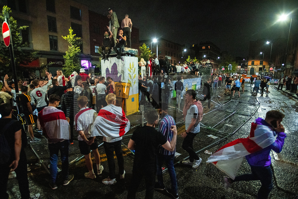 © Licensed to London News Pictures . 11/07/2021. Manchester, UK. Fencing, erected to prevent fans from sitting on street furniture in the square is seen lying on the ground after it was pulled apart . England football fans are seen reacting in Stevenson Square in Manchester City Centre after England lose on penalties after extra time in the European Cup Final match between England and Italy , which was played at Wembley Stadium. Photo credit: Joel Goodman/LNP