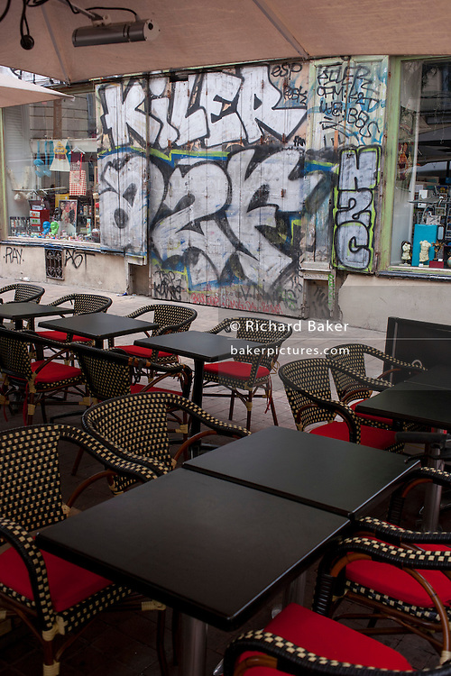 Vacant cafe seating and a background of graffiti and dirty walls in Montpellier, south of France.
