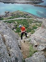 """En klatrer på rapell ned fra ruta """"Pianohandler Lunds rute"""" i Lofoten, A climber is rapelling down from the route """"Pianohandler Lunds rute"""" in Lofoten"""