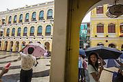 People walking while raining at the Senado Square (Largo do Senado).