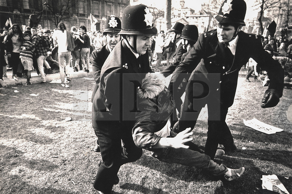 © Licensed to London News Pictures. 25/03/2020. London, UK. In this image from March 31st 1990 police detain a protester outside the Ministry of Defence during the London poll tax riots. The protest on the last day of March in 1990 started peacefully when thousands gathered in a south London park to demonstrate against Margaret Thatcher's Government's introduction of the Community Charge - commonly known as the poll tax. Marchers walked to Whitehall and Trafalgar Square where violence broke out with the trouble spreading up through Charring Cross Road and on to the West End. Police estimated that 200,000 people had joined the protest and 339 were arrested. The hated tax was eventually replaced by the Council Tax under John Major's government in 1992.  Photo credit: Peter Macdiarmid/LNP