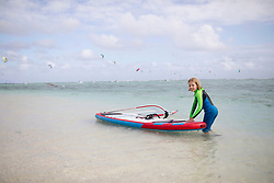 Girl with surfboard in ocean, Mauritius