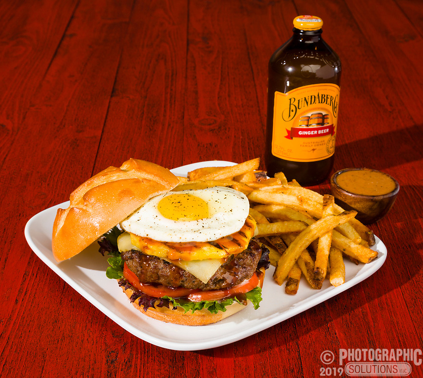 Hamburger with fried egg, fries and a root beer