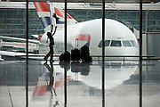"""A young girl in transit between India and the US, entertains herself by throwing her pet toy tiger as far as the ceiling in a departure window of Heathrow Airport's Terminal 5. In front of a Boeing 777 jet airliner's nose and cockpit, the girl is a silhouette against the large windows that allow in the natural light. Behind the parked aircraft, another British Airways passenger jet taxies past, its tail at right-angles to the stationary airplane although they both look like the same plane. With her family baggage next to her, the child is enjoying some hours of freedom before another long-haul flight westwards. From writer Alain de Botton's book project """"A Week at the Airport: A Heathrow Diary"""" (2009)."""