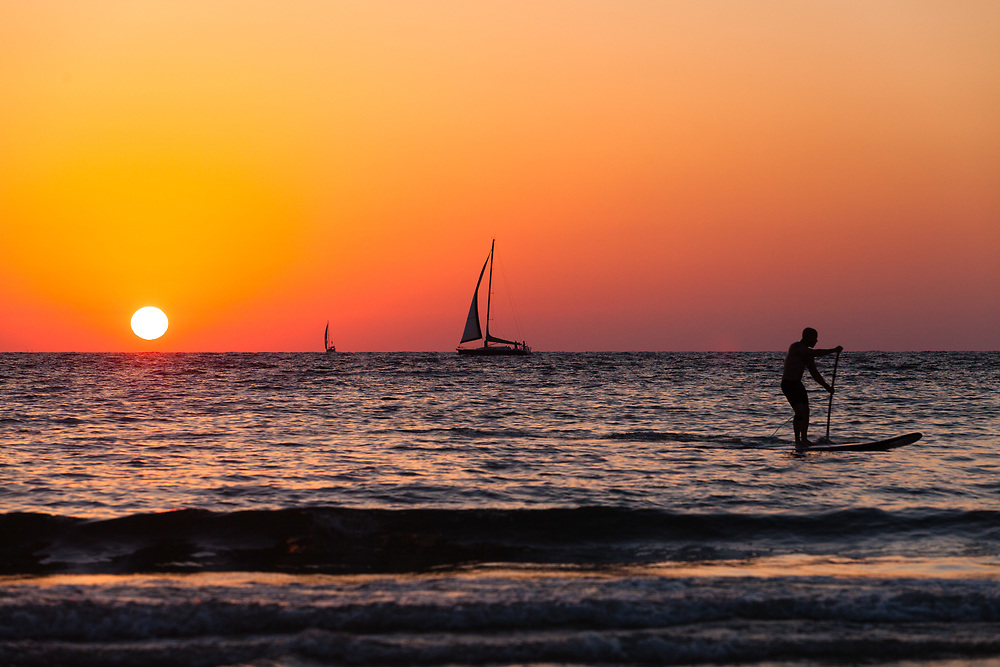 A paddleboarder and boats are silhouetted during sunset at the Mediterranean Sea near Gordon Beach in Tel Aviv, Israel, on July 21, 2015.