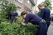 Nederland, Nijmegen, 5-8-2004..In de buurt van de woning van een vermoorde man doet de politie, me, onderzoek, gezocht wordt naar het moordwapen. sporenonderzoek, misdaad, moord, politie, onderzoek, zwaar misdrijf, oplossen misdaad. Buurtonderzoek...Foto: Flip Franssen/Hollandse Hoogte