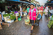 """26 SEPTEMBER 2012 - BANGKOK, THAILAND: 26 SEPTEMBER 2012 - BANGKOK, THAILAND:   A porter walks through Khlong Toey Market in Bangkok. Khlong Toey (also called Khlong Toei) Market is one of the largest """"wet markets"""" in Thailand. The market is located in the midst of one of Bangkok's largest slum areas and close to the city's original deep water port. Thousands of people live in the neighboring slum area. Thousands more shop in the sprawling market for fresh fruits and vegetables as well meat, fish and poultry.   PHOTO BY JACK KURTZ     PHOTO BY JACK KURTZ"""