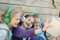 Three friends sitting in playground and listening music, Munich, Bavaria, Germany