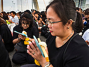05 DECEMBER 2016 - BANGKOK, THAILAND:  People on Bhumibol Bridge pray during a ceremony honoring the late King of Thailand. Tens of thousands of Thais gathered on Bhumibol Bridge in Bangkok Monday to mourn the death of Bhumibol Adulyadej, the Late King of Thailand. The King died on Oct 13 after a lengthy hospitalization. December 5 is his birthday and a national holiday in Thailand. The bridge is named after the late King, who authorized its construction. 999 Buddhist monks participated in a special merit making ceremony on the bridge.      PHOTO BY JACK KURTZ