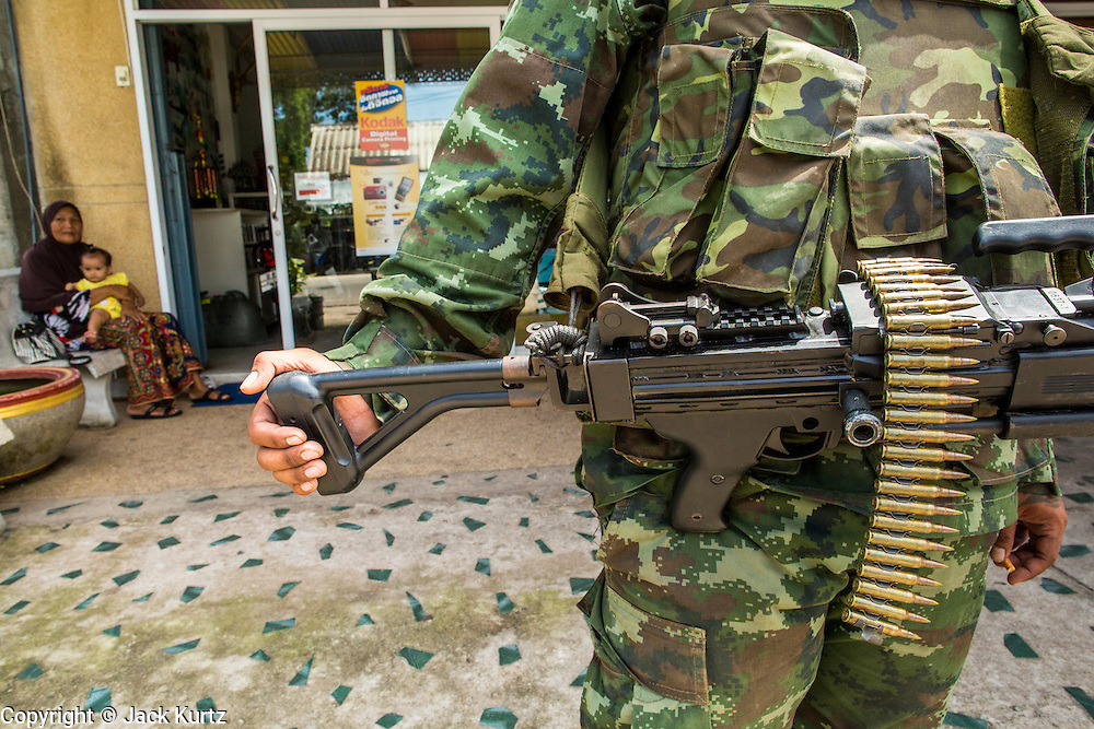 """25 OCTOBER 2012 - TAK BAI, NARATHIWAT, THAILAND: A soldier in the Royal Thai Army armed with MINI (machinegun) in front of a Muslim convenience store in Tak Bai, Thailand. The """"Tak Bai Incident"""" took place on Oct. 25 in Tak Bai, Narathiwat, Thailand during the Muslim insurgency in southern Thailand. On that day, a crowd gathered to protest the arrest of local residents. Police made hundreds of arrests during the protest and transported the arrested to Pattani, about two hours away, in another province. They were transported in locked trucks and more than 80 people suffocated en route. This enraged local Muslims and shocked people across Thailand. No one in the Thai army accepted responsibility for the deaths and no one was ever charged. In the past, the anniversary of the incident was marked by protests and bombings. This year it was quiet. More than 5,000 people have been killed and over 9,000 hurt in more than 11,000 incidents, or about 3.5 a day, in Thailand's three southernmost provinces and four districts of Songkhla since the insurgent violence erupted in January 2004, according to Deep South Watch, an independent research organization that monitors violence in Thailand's deep south region that borders Malaysia.   PHOTO BY JACK KURTZ"""