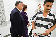 """06 NOVEMBER 2006 - PHOENIX, AZ: Maricopa County Sheriff JOE ARPAIO hands out certificates on completion to Spanish speaking prisoners who complete a two week English class in the county jail. Sheriff Joe Arpaio is offering intensive two week English classes in the Maricopa County Jails so county prisoners can communicate with Detention Officers. The classes teach """"jail English"""" so inmates can report medical problems, request their lawyers, request bedding etc. There are more than 1,000 illegal immigrants in the county jail system. In 2011, the US Department of Justice issued a report highly critical of the Maricopa County Sheriff's Department and the jails. The DOJ said the Sheriff's Dept. engages in widespread discrimination against Latinos during traffic stops and immigration enforcement, violates the rights of Spanish speaking prisoners in the jails and retaliates against the Sheriff's political opponents.      PHOTO BY JACK KURTZ"""