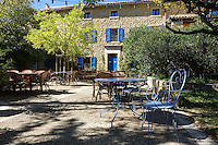 Blue chairs and tables in an outdoor terrace at a restaurant in Seguret, Provence, France are surrounded by olive trees. Blue shutters on the stone wall of the cafe match the colors of the chairs.