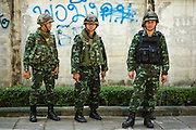 """01 FEBRUARY 2014 - BANGKOK, THAILAND: Thai soldiers on a sidewalk near a closed polling place in Bangkok. Thais went to the polls in a """"snap election"""" Sunday called in December after Prime Minister Yingluck Shinawatra dissolved the parliament in the face of large anti-government protests in Bangkok. The anti-government opposition, led by the People's Democratic Reform Committee (PDRC), called for a boycott of the election and threatened to disrupt voting. Many polling places in Bangkok were closed by protestors who blocked access to the polls or distribution of ballots. The result of the election are likely to be contested in the Thai Constitutional Court and may be invalidated because there won't be quorum in the Thai parliament.    PHOTO BY JACK KURTZ"""