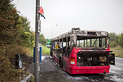 © Licensed to London News Pictures . 25/09/2013 . Brighton , UK . A melted bus stop sign by the ruined bus . The burned out remains of a Brighton-bound bus that caught fire minutes before the firefighters strike had ended , on the A23 this afternoon (25th September 2013) . The smoke filled road was closed to traffic causing large tailbacks . Photo credit : Joel Goodman/LNP