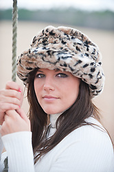Portrait of a young woman in a fur hat holding onto a rope