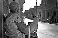 An elderly woman is watching the street with her dog in Santa Clara.