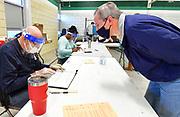 Election judge Tom Wade (left) checks the registration information for voter Brian Rodenmeyer of Belleville at Douglas School in Belleville. Rodenmeyer was voting in precinct 25 on Tuesday, November 3, 2020.  <br /> Photo by Tim Vizer