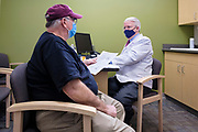 05 JANUARY 2021 - URBANDALE, IOWA: Pharmacist JOHN FORBES (right) and Dr. DAVID DAVIDSON talk about follow up procedures to receive the second dose of Moderna GOVID-19 vaccine. Forbes had just given Davidson the first dose at the Medicap Pharmacy in Urbandale. The pharmacy received about 500 doses of the Moderna vaccine and is vaccinating medical workers in accordance with Iowa guidelines. Forbes, who owns and operates the pharmacy, said that they were vaccinating about 30 people per day and that the initial shipment of vaccines should last for about 11 days. The Moderna vaccine prevents infection from the Coronavirus.      PHOTO BY JACK KURTZ