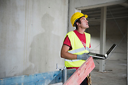 Construction worker with laptop at building site, Munich, Bavaria, Germany