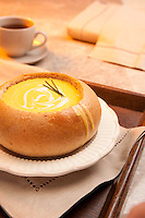 A tasty bread bowl filled with cheese soup.