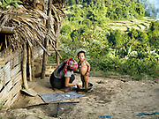 An Akha Nuquie ethnic minority woman washes her young daugher outside her bamboo home in Ban Km 62 village, Phongsaly Province, Lao PDR. One of the most ethnically diverse countries in Southeast Asia, Laos has 49 officially recognised ethnic groups although there are many more self-identified and sub groups. These groups are distinguished by their own customs, beliefs and rituals. Details down to the embroidery on a shirt, the colour of the trim and the type of skirt all help signify the wearer's ethnic and clan affiliations.