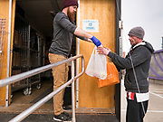 """26 MARCH 2020 - DES MOINES, IOWA: ANDREW FIRESTINE, a DMARC staff member hands food packages to a client at a Des Moines Area Religious Council (DMARC) mobile pantry food distribution in the DART Central Station in Des Moines. Clients were asked to keep a safe distance and remain on the far side of the metal bar. DMARC is doing weekly food distribution at the transit station. They are using """"social distancing"""" guidelines by asking clients to not get too close to their workers. DMARC used to let clients walk through mobile pantry to select groceries, but now clients wait while workers bags of foodstuffs. On Thursday morning, 24 March, Iowa reported 175 confirmed cases of the Coronavirus (SARS-CoV-2) and COVID-19. Restaurants, bars, movie theaters, places that draw crowds are closed until 07 April. The Governor has not ordered """"shelter in place""""  but several Mayors, including the Mayor of Des Moines, have asked residents to stay in their homes for all but the essential needs. People are being encouraged to practice """"social distancing"""" and many businesses are requiring or encouraging employees to telecommute.       PHOTO BY JACK KURTZ"""