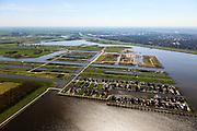 Nederland, Groningen, Oldambt, 01-05-2013; Blauwestad, nieuw aangelegd woongebied inclusief recreatiegebied. Het Oldambtmeer dient ook als waterberging. In de voorgrond wijk  'De Wei' met kavels voor zelfbouw., daar achter de nog onbebouwd wijk 'het Dorp'. In de verre achtergrond het informatie en verkoopcentrum, Winschoten aan de horizon.<br /> Het project Blauwe Stad was oorspronkelijk bedoeld om de economisch achtergebleven regio van Noordoost Groningen een impuls te geven. De economische en huizen crisis gooit echter roet in het eten.<br /> Blauwestad (Blue City) newly constructed residential area, including recreational lake. The Oldambt lake also serves as water storage. In the foreground 'De Wei' (Meadow) with plots suited for 'DIY' buidling of houses, in the background  the still undeveloped area 'the Village' and the information and sales center.<br /> The Blue City project is meant to give a boost to the  economically backward region of northeast Groningen.<br /> luchtfoto (toeslag); aerial photo (additional fee required);<br /> foto Siebe Swart / photo Siebe Swart