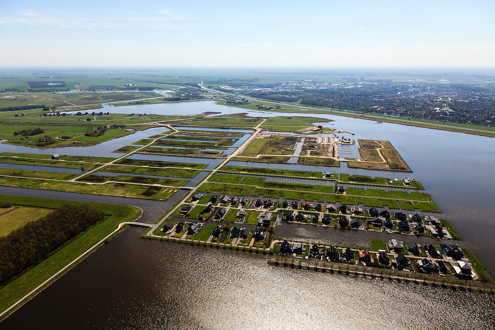 Nederland, Groningen, Oldambt, 01-05-2013; Blauwestad, nieuw aangelegd woongebied inclusief recreatiegebied. Het Oldambtmeer dient ook als waterberging. In de voorgrond wijk  'De Wei' met kavels voor zelfbouw., daar achter de nog onbebouwd wijk 'het Dorp'. In de verre achtergrond het informatie en verkoopcentrum, Winschoten aan de horizon.<br /> Het project Blauwe Stad was oorspronkelijk bedoeld om de economisch achtergebleven regio van Noordoost Groningen een impuls te geven. De economische en huizen crisis gooit echter roet in het eten.<br /> Blauwestad (Blue City) newly constructed residential area, including recreational lake. The Oldambt lake also serves as water storage. In the foreground 'De Wei' (Meadow) with plots suited for 'DIY' buidling of houses, in the background  the still undeveloped area 'the Village' and the information and sales center.<br /> The Blue City project is meant to give a boost to the  economically backward region of northeast Groningen.<br /> luchtfoto (toeslag); aerial photo (additional fee required);<br /> foto Siebe Swart / photo Siebe Swart