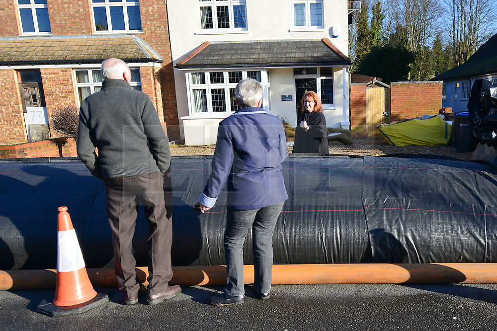 """© Licensed to London News Pictures. 16/02/2014. Chertsey, UK. Neighbours talk over the dam which they affectionately call """"the Sausage"""". An Aqua dam has been erected along Bridge Road in Chertsey, Surrey. At almost half a mile long and four feet high the dam is designed to protect 200 houses on the South Side of the street. The Environment Agency has said there is nothing they can do to protect the houses on the North side if flood water from the River Thames rises. . Photo credit : Stephen Simpson/LNP"""