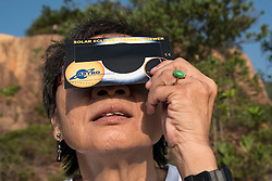 © Licensed to London News Pictures. 09/03/2016 Ipoh, Malaysia. A woman watches a partial solar eclipse over the city of Ipoh in Malaysia, Wednesday, March 9, 2016. Photo credit : Sang Tan/LNP
