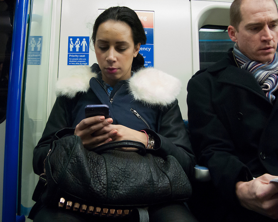 Portrait of female Londoner on the underground looking at her mobile device