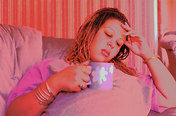 Pregnant young woman sitting on sofa holding cup of tea looking tired,