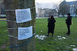 © Licensed to London News Pictures;13/03/2021; Bristol, UK. Signs attached to trees are seen as flowers and notes in remembrance have been laid on College Green in memory of woman Sarah Everard whose body was confirmed found in Kent yesterday. A police officer has been charged with her murder. Vigils across the the country had been planned but were cancelled because of the Covid-19 coronavirus pandemic Lockdown restrictions in England. Photo credit: Simon Chapman/LNP.