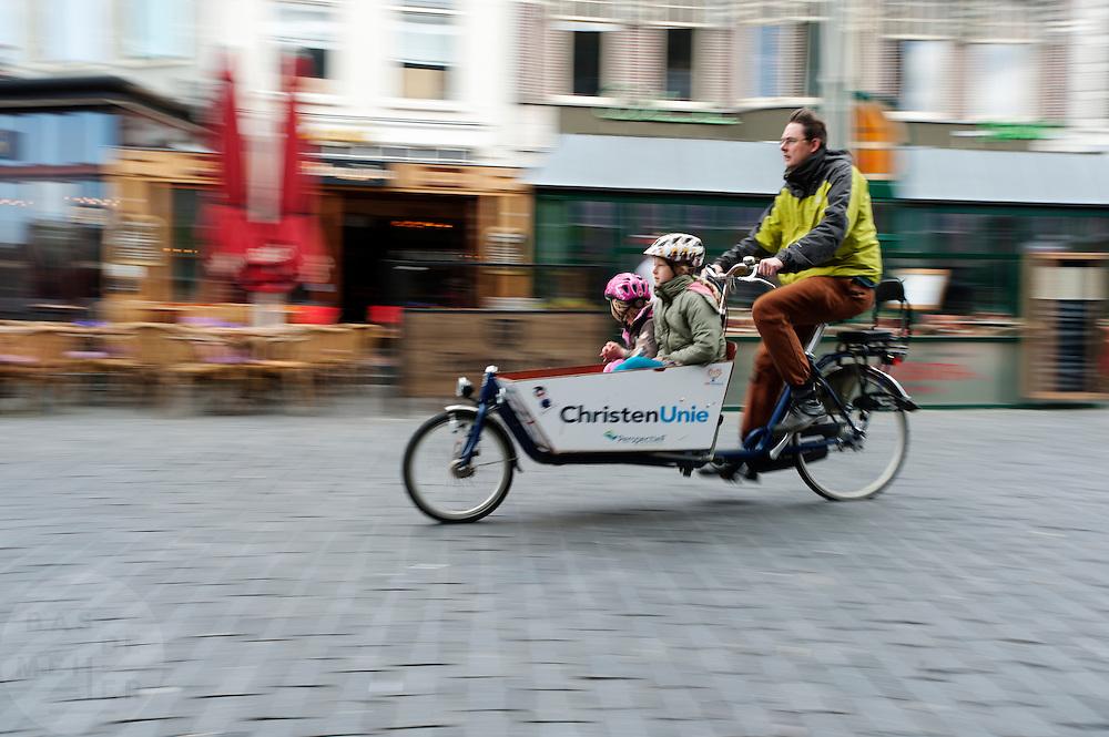 In Nijmegen fietst een partijlid van de ChristenUnie met zijn kinderen in de bakfiets door de binnenstad. Bakfietsen worden in heel Europa steeds vaker ingezet, zowel door particulieren als bedrijven. Het is een duurzame vorm van transport en biedt veel voordelen.<br /> <br /> In Nijmegen a member of the ChristenUnie cycles with his kids in a cargo bike. Cargo bikes are increasingly being deployed across Europe, both individuals and businesses. It is a sustainable form of transport and offers many advantages.