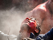 12 MARCH 2017 - BHAKTAPUR, NEPAL: A Nepali man stands under the spray of hose during Holi celebrations in Bhaktapur. Holi, a Hindu religious festival, has become popular with non-Hindus in many parts of South Asia, as well as people of other communities outside Asia. The festival signifies the victory of good over evil, the arrival of spring, end of winter, and for many a festive day to meet others. Holi celebrations in Nepal are not as wild as they are in India.     PHOTO BY JACK KURTZ