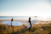Surfers standing in the sand dunes with their surf boards at Le Braye, in front of La Rocco Tower, St Ouen's Bay, Jersey, CI