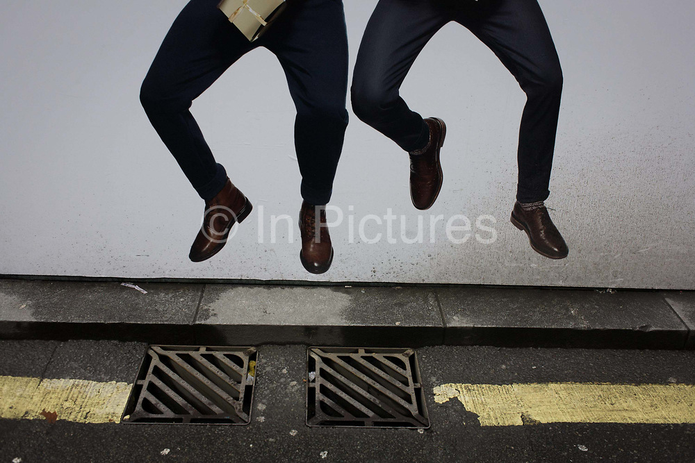 Leaping models advertise clothing retailer H&M above street drain covers in central London. The two men a pictured in mid-air - jumping up while holding Christmas gifts and looking happy to have spent their money during the Xmas retail frenzy. The hoarding that screens off construction work on Oxford Street, is next to the drains that the men appear to be dancing over. In 1947 Hennes women's clothing store opened in Västerås, Sweden. Today the H&M Group offers fashion for everyone under the brands of H&M, COS, Monki, Weekday, Cheap Monday and & Other Stories, as well as fashion for the home at H&M Home.