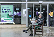 21st February, Cheltenham, England. A man sat on a bench reading a newspaper in the Promenade area of Cheltenham.