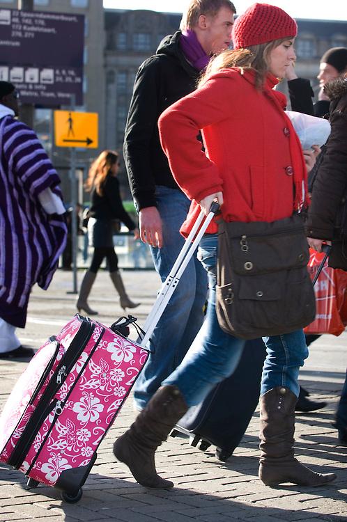 Nederland, Amsterdam, 26 febr 2008.Voor het centraal station van amsterdam. Toeristen op weg naar trein slepen rolkoffers met zich mee..Foto (c) Michiel Wijnbergh