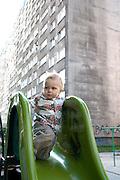 Apprehensive toddler on park slide. Blok housing behind a reminder of the communist era. Balucki District Lodz Central Poland