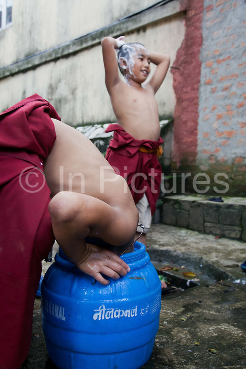 Young monks in a Tibetan monestary at the Swayambhunath temple complex, also called the Monkey Temple. The young boys are having their hair shaved by an older monk. One of the boys has had his head shaved and is now rinsing out the foam by sticking his head into a plastic barrel with water.