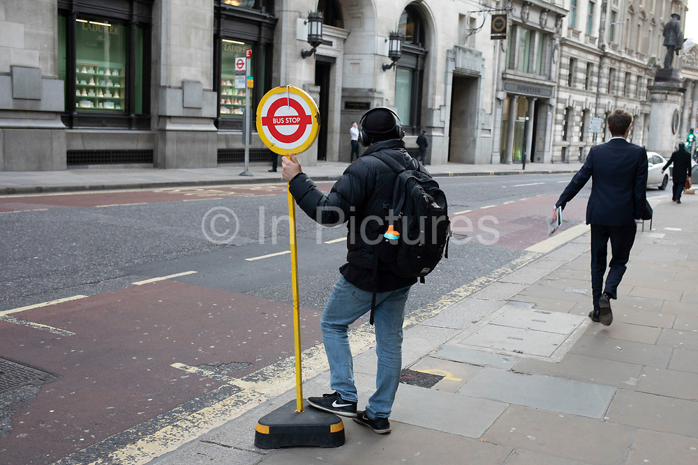 Man holding on waiting at a temporary bus stop in the City of London on 5th February 2020 in London, England, United Kingdom. The City of London is a city, county and a local government district that contains the historic centre and the primary central business district CBD of London.
