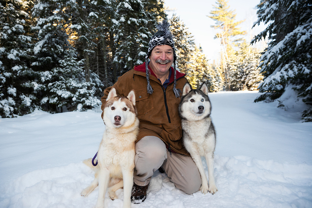 Portrait of a musher and two of his Siberian Huskies