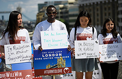 © Licensed to London News Pictures. 03/06/2018. London, UK. Campaigners from Turn To Love hold up personal signs ahead of a minutes silence for the victims of the 2017 London Bridge Terror attack, held on London Bridge. Eight people were killed and 48 were injured when a van was deliberately driven into pedestrians on London Bridge. Three occupants then ran to the nearby Borough Market area carrying knives and fake explosives. Photo credit: Ben Cawthra/LNP
