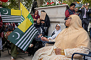 Women wearing traditional saris waving Kashmiri flags during a pro Kashmir protest at Parliament Square on the 3rd September 2019 in London in the United Kingdom. Protesters gather near the statue of Mahatma Gandhi in solidarity following Indian Prime Minister Narendra Modi's Independence Day speech removing special rights of Kashmir as an autonomous region.