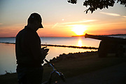 A you man is catching Pokemons near a canon by the citadel in the setting sun by the sea in Landskrona, Sweden, 27th of August 2016.