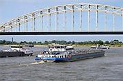 Nederland, Nijmegen,7-7-2018 Binnenvaartschepen, beladen met o. a. kolen, varen over de Waal langs Nijmegen. Op de achtergrond de oude Waalbrug . Het water staat laag en het is druk .Foto: FOTO: FLIP FRANSSEN